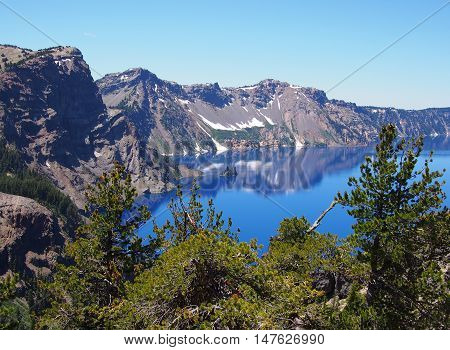 Jagged Crater Lake Rim reflects in the beautiful blue lake.