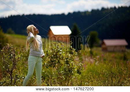 young beautiful woman in blue dress the heather meadows in Scotland watching the mountains.