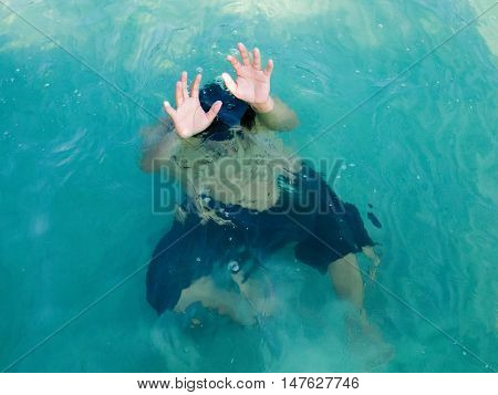 Drowning man in sea asking for help with raised his arms. Safety concept.