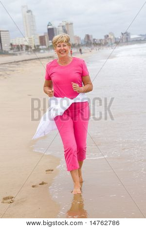 Active and happy senior woman running on beach for exercise
