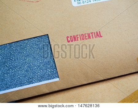 """Red """"Confidential"""" word printed on brown vintage envelope in macro. Business confidential concept. poster"""