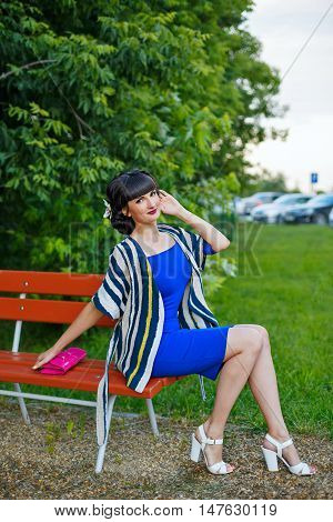 Young attractive girl sitting on a bench in a park in blue dress.