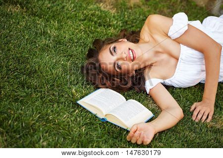 Lovely girl reading a book lying on a green lawn. Romantic and poetic girl smiling.