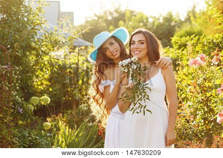 Two sisters. Girl holding a bouquet of flowers. Sister hugging her. In the backyard. Family time. Human relationships. Setting sun.