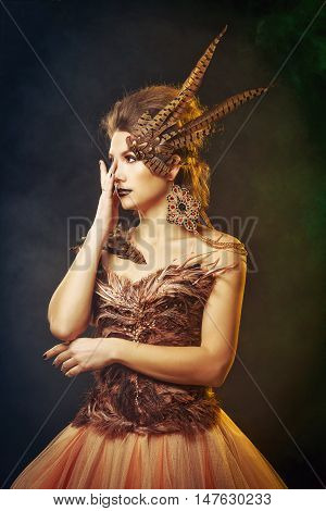 Girl harpy. Creative makeup for Halloween. The concept of magic creature. Mystical.