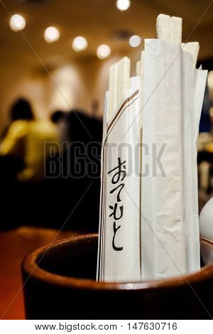 Disposable chopsticks in holder. Image has shallow depth of field, focusing on portions of the Japanese Hiragana characters (Otemoto - meaning chopsticks) on the sleeves.