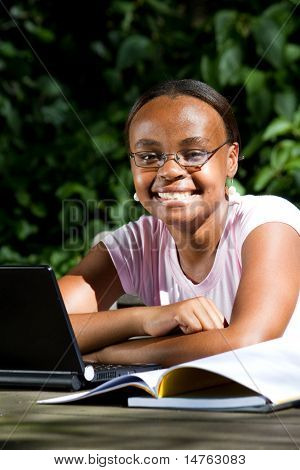 happy african american female student studying computer outdoors