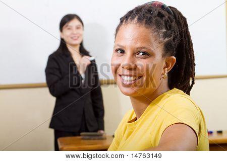 afrikanischer Studierender im Klassenzimmer, Hintergrund ist ein Lehrer steht vor der Tafel