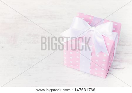 Gift box wrapped in pink dotted paper and tied satin bow over a white wood background.