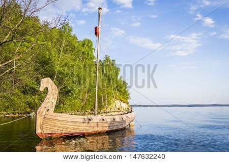Ancient wooden ship is in a bay near the pier.