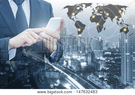 Double Exposure Of Businessman Connect Internet Smart Phone & Cityscape Of Business With World Finan