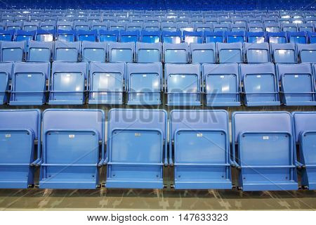 Many rows of blue empty seats with numbers in big modern sport stadium