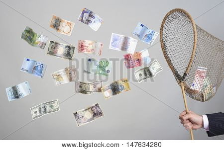 Closeup of hand holding butterfly net with flying banknotes against gray background