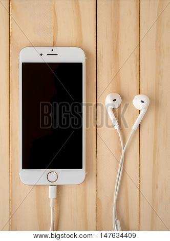 CHIANGRAI THAILAND -SEPTEMBER 15 2016: Front view image of new Apple iPhone7 mockup and new Apple EarPods mockup on wooden background. Vertical.