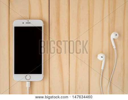 CHIANGRAI THAILAND -SEPTEMBER 15 2016: Front view image of new Apple iPhone7 mockup and new Apple EarPods mockup on wooden background with copy space.