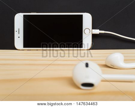 CHIANGRAI THAILAND -SEPTEMBER 15 2016: Front view of new Apple iPhone7 mockup leaning against on black background and connecting with new Apple Lightning EarPods mockup on wooden table.