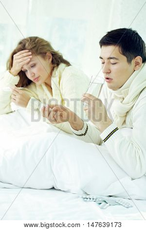 Ill family couple lying in bed and taking medicine