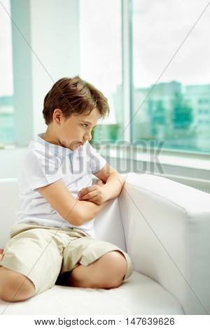 Little sulky boy sitting on sofa