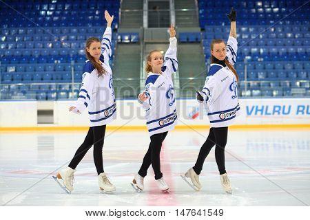 MOSCOW, RUSSIA - 14 OCT, 2015: Three girls perfrom on ice rink at hockey meet Dinamo Balashikha and Izhstal