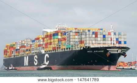 Oakland CA - September 12 2016: Multiple tugboats assist Cargo Ship MSC ARIANE to manuever into the Port of Oakland the fifth busiest port in the United States.
