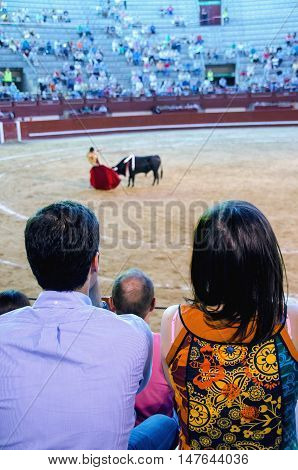 Spectators in the bullring are viewing how the bullfighter give a pass to the bull. Corrida de toros