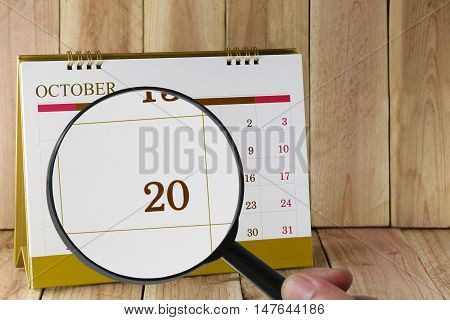 Magnifying glass in hand on calendar focus you can look number 20 in October to Concept in business and meetings.