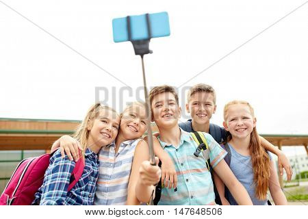 primary education, technology, friendship, childhood and people concept - group of elementary school students with backpacks sitting on bench and taking picture by smartphone on selfie stick outdoors