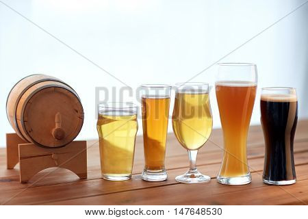 brewery, drinks and alcohol concept - close up of different beers in glasses and barrel on table