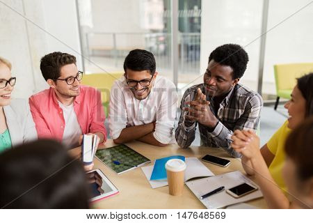 education, high school, people and technology concept - group of international students sitting at table with tablet pc computer, smartphones and notebooks and talking at university