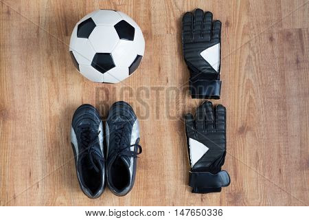 sport, soccer, football and sports equipment concept - close up of ball, boots and goalkeeper gloves on wooden background