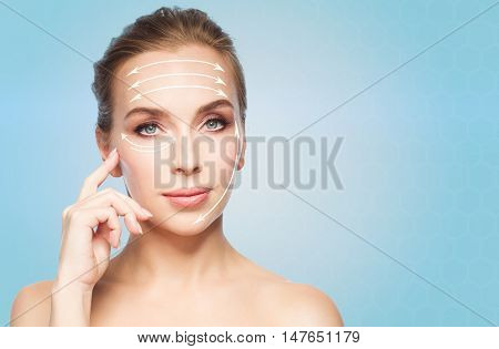 beauty, people , plastic surgery and anti-age concept - beautiful young woman showing her cheekbone over blue background