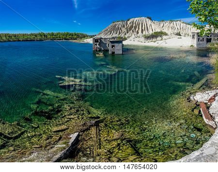 Abandoned mines and hauses. Quarry and old prison architecture. Crystal clear blue water lake and mountain. The ashes dunes in Estonia Europe.