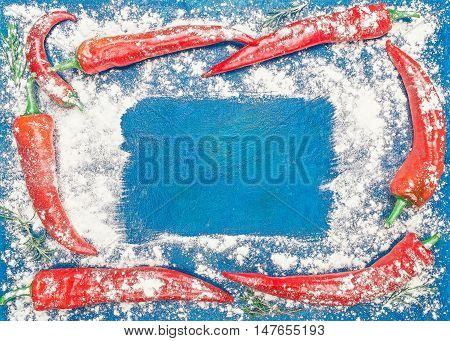 Frame of red chile pepper and potherb branches under the flour over blue background. Flat lay. Color toning