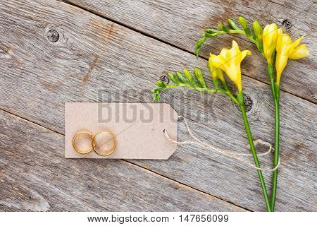 Yellow freesia flowers with blank tag and wedding rings on old wooden background
