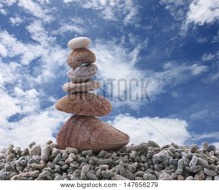 Balance stone on dead coral and have blue sky background.