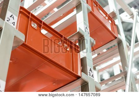Red plastic boxes in the cells of the automated warehouse. Metal construction warehouse shelving.