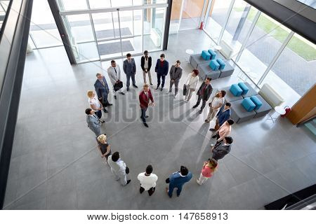 Young director has meeting with employees in circle in company hall