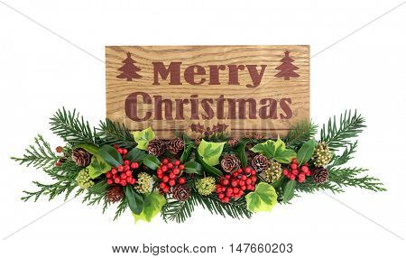Merry christmas rustic wooden sign with floral decoration of holly and red berries, ivy, pine cones, cedar cypress and fir leaf sprigs over white background.
