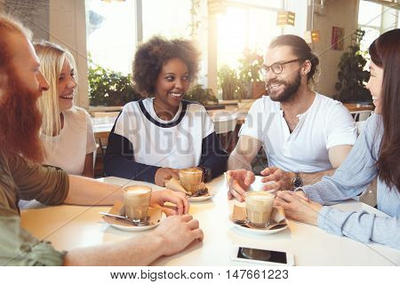 Young Happy Hipster-looking Stylish People Of Diverse Ethnicities Sitting At Cafeteria, Chatting, Sm