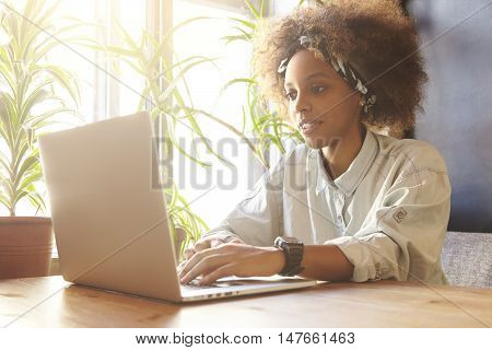 People And Technology. Young African Woman Freelancer In Denim Shirt And Bandana Working On Laptop C