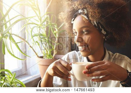 People And Leisure. African Woman Dressed In Trendy Clothes Holding Cup Of Coffee Or Tea, Enjoying H