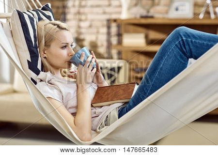 Young woman resting in hammock at home, drinking tea.