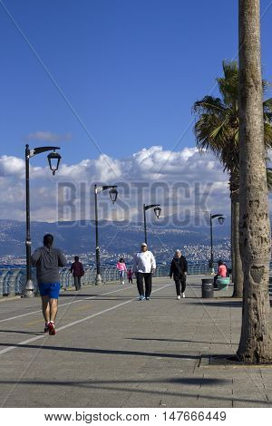 The famous seaside Corniche on sunset, Beirut, Lebanon. Beirut, Lebanon - January 09, 2016:  People take their sunset walk on the famous Corniche (seaside promenade) in Beirut, Lebanon
