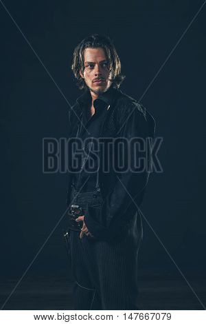 Retro 1900 Western Man. Young Adult. Studio Shot Against Dark Background.