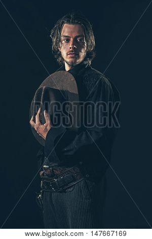 Vintage Cowboy Holding Hat In Hand. Young Man. Studio Shot.