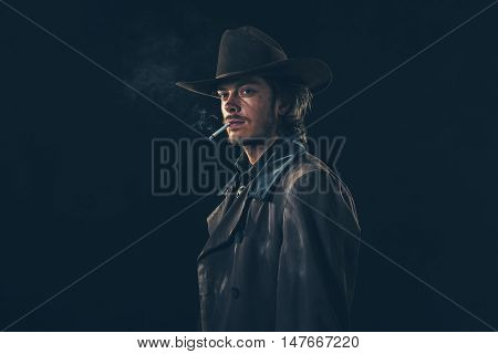Retro Cowboy Smoking Cigarette. Young Man. Studio Shot.
