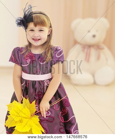 Nice little girl dressed in brown dress. She is holding a bouquet of maple leaves.In the children's room where sits a large Teddy bear .