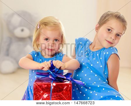 Two charming little girls , sisters, in identical blue dresses with polka dots. Girl looking at gifts Packed in beautiful red paper tied with a bow.In the background children's room where the sitting Teddy bear.