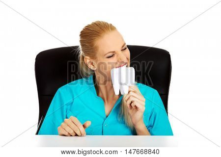 Funny female dentist sitting behing the desk and holding oversized tooth model