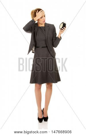 Worried business woman holding alarm clock